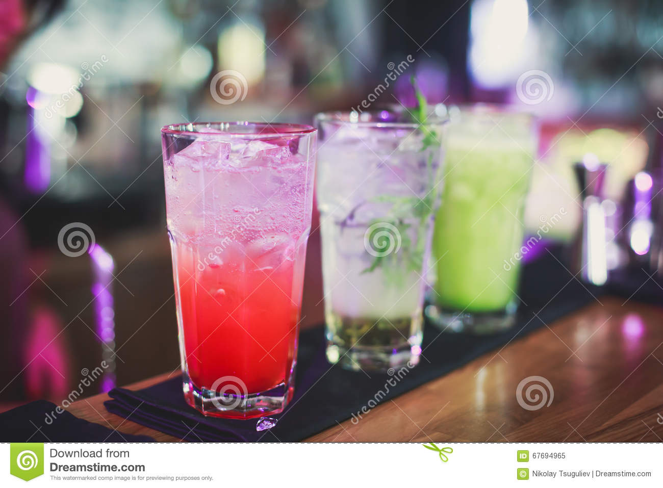 Beautiful line of different colored alcohol cocktails with smoke on a Christmas party, tequila, martini, vodka, and others on part