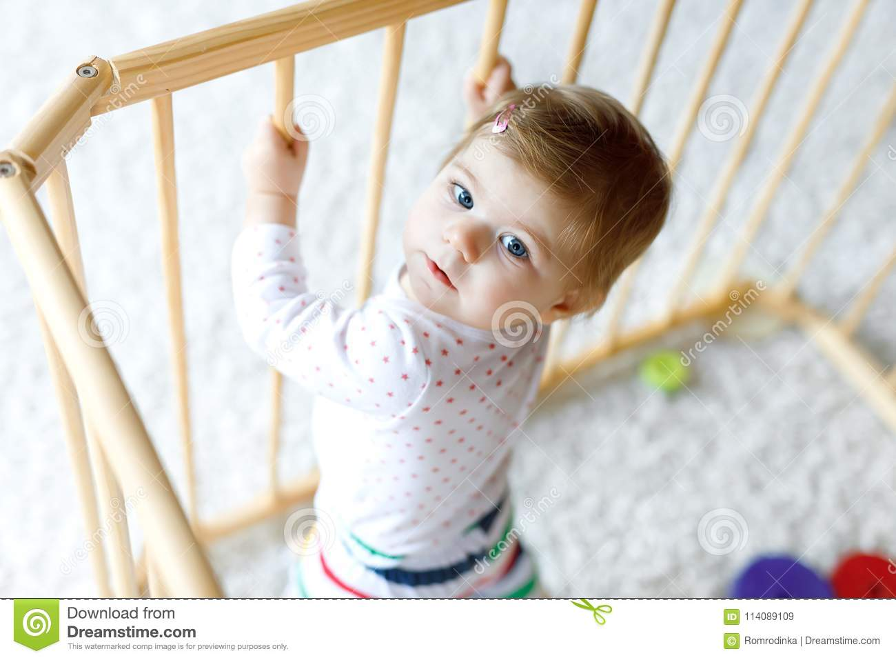 bd0dd9c04 Beautiful little baby girl standing inside playpen. Cute adorable child  playing with colorful toy