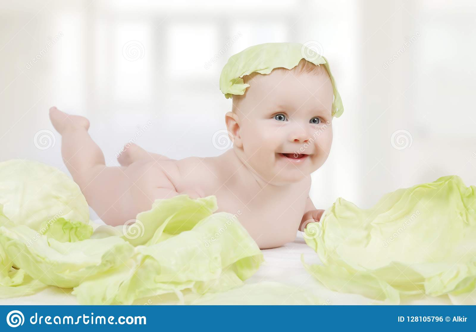 Beautiful little baby with green cabbage