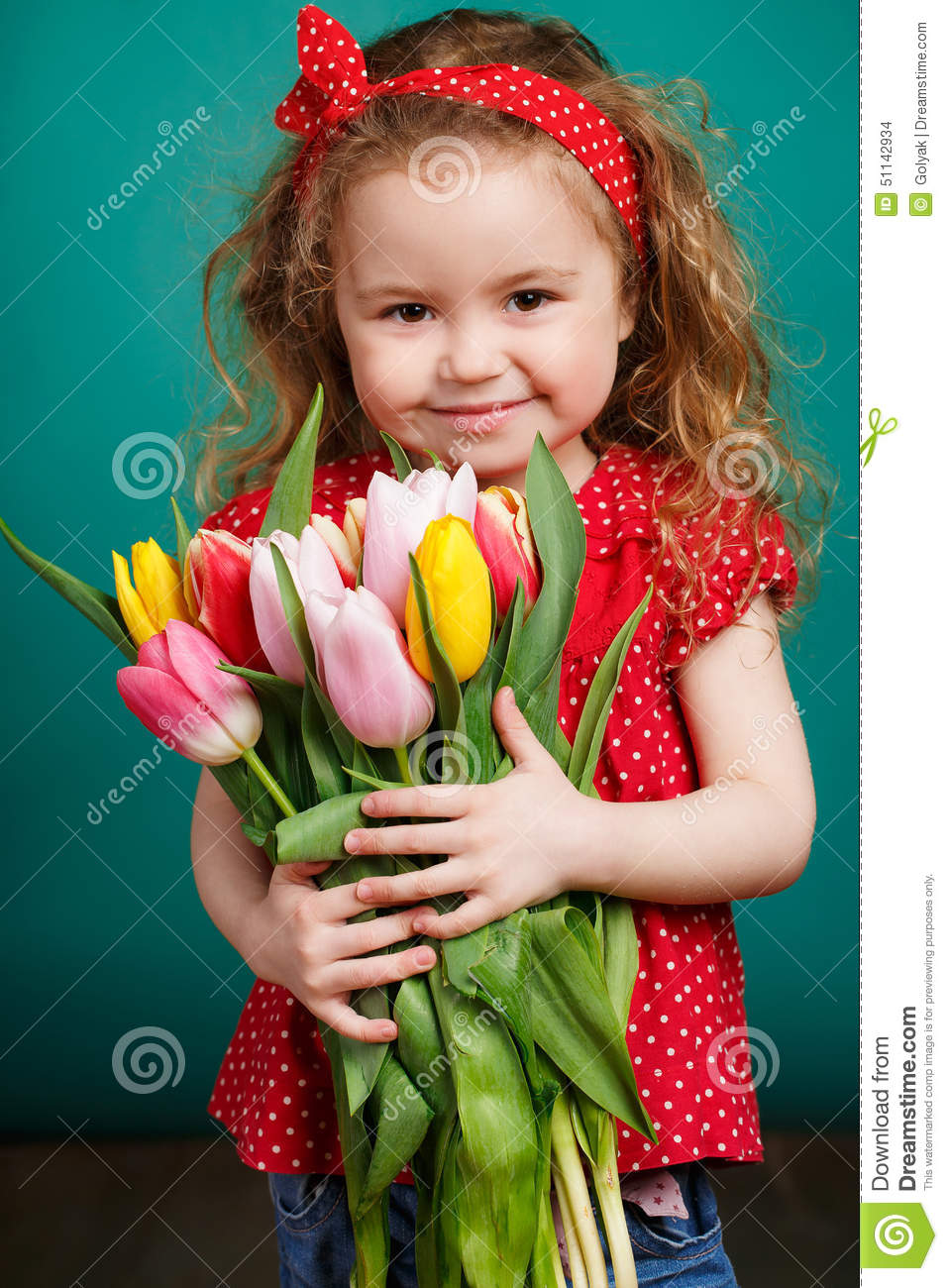 Beautiful little girl with a big bouquet of tulips.
