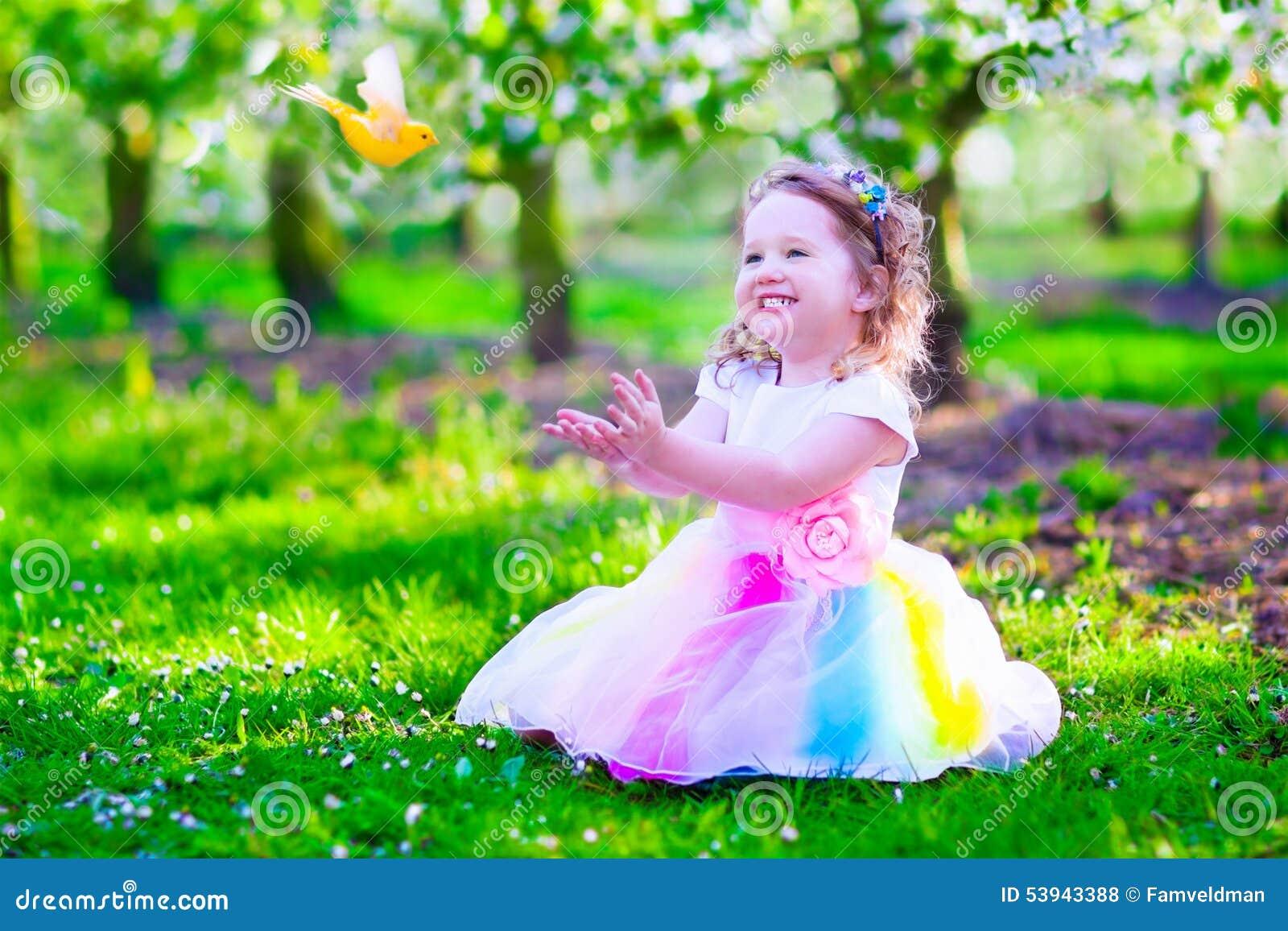Great Beautiful Little Girl In Fairy Costume Feeding A Bird