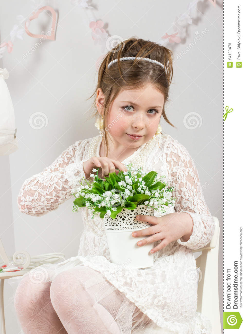 A Beautiful Little Girl With Flowers In A Pot Stock Image