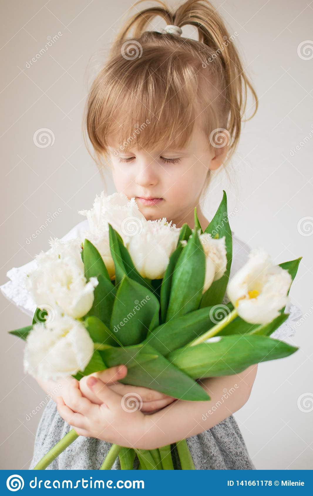 Beautiful little girl holding a bouquet of flowers