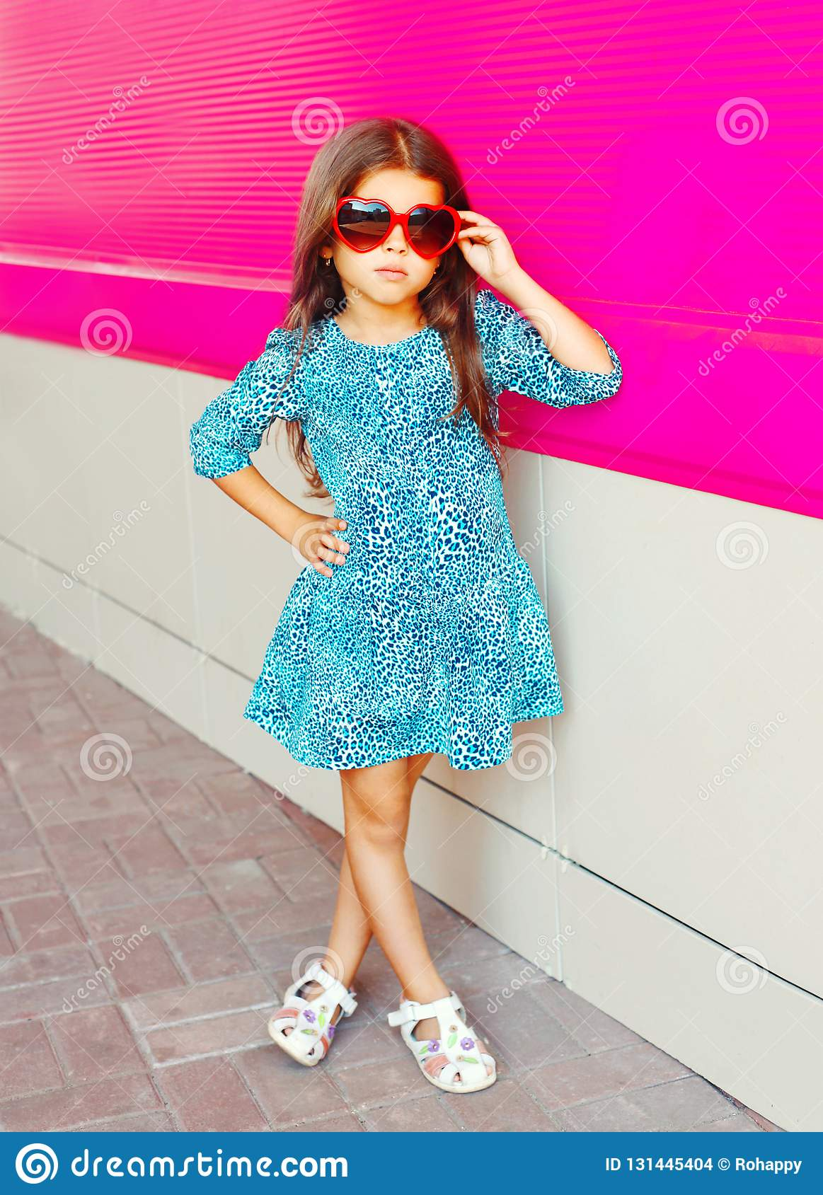 Beautiful little girl in leopard print dress on colorful pink