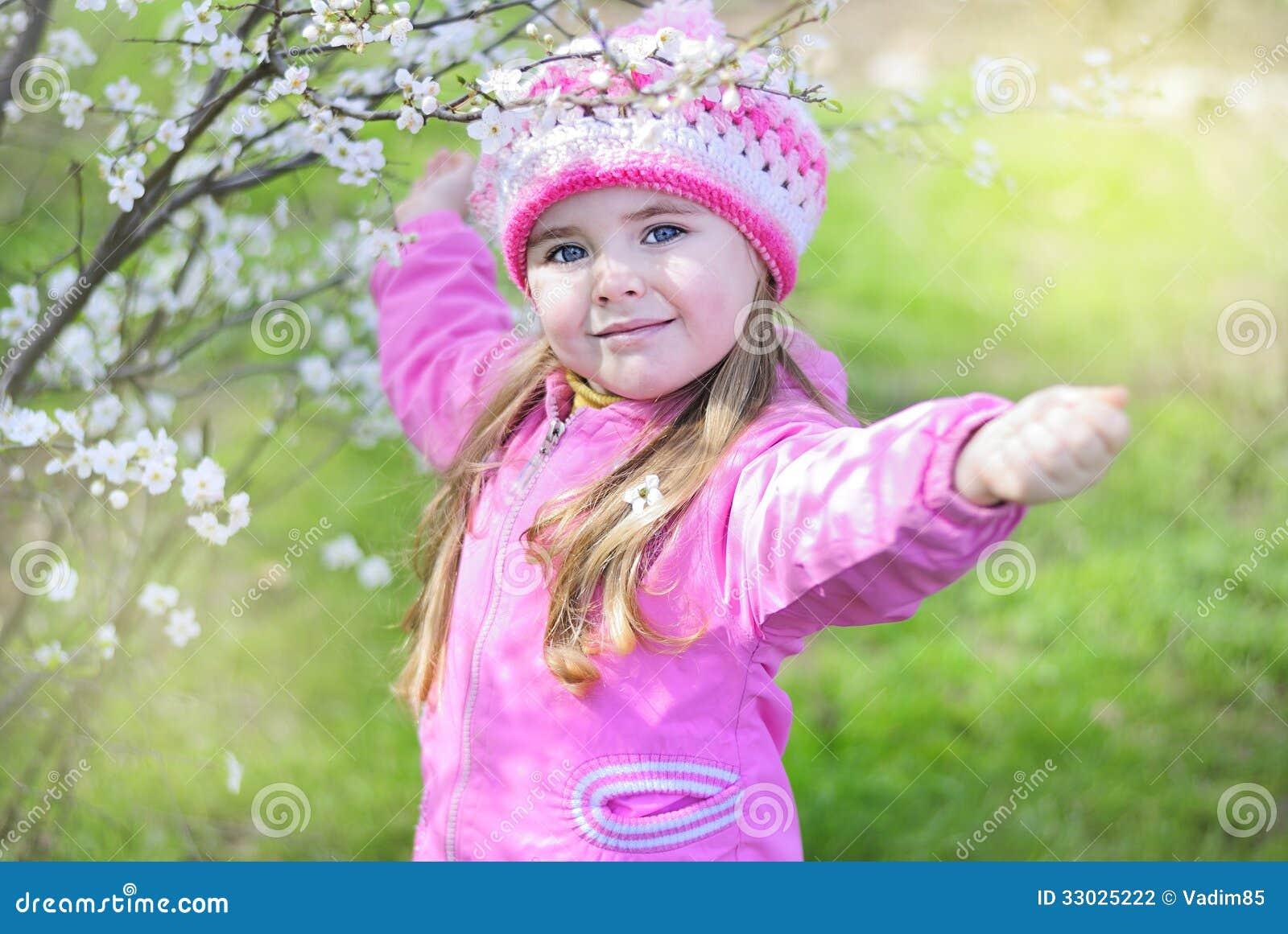 beautiful little girl near a flowering tree stock