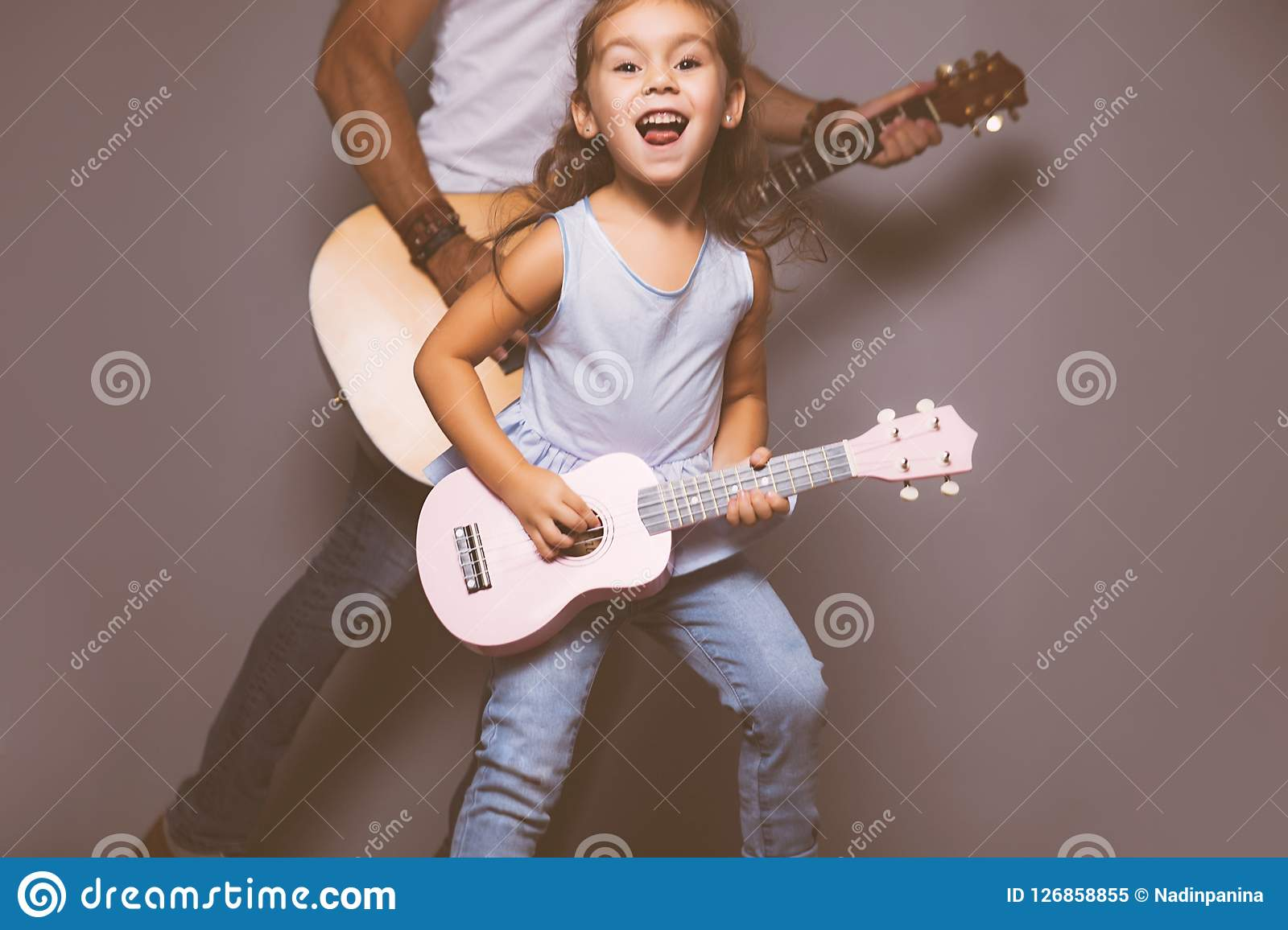 Beautiful Little Girl Playing Guitar With Her Father  Stock