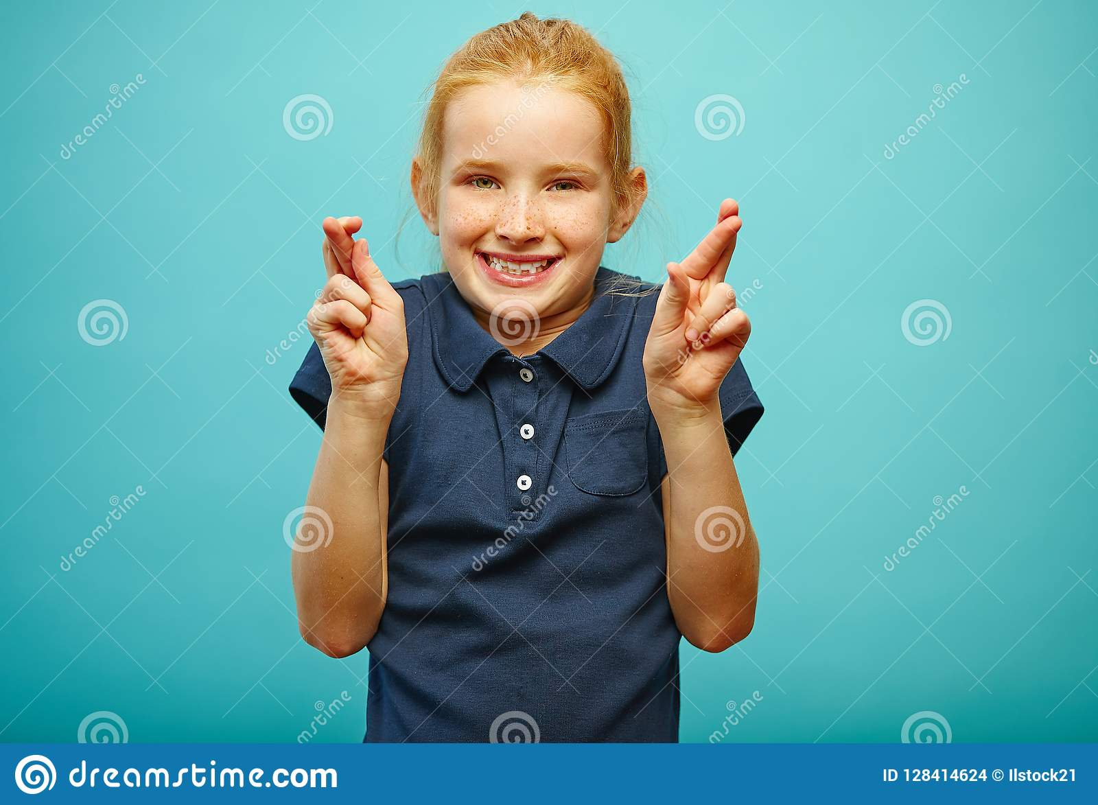 Beautiful little girl with red hair and freckles makes a wish, fingers crossed, believes in fulfillment of dreams, has a