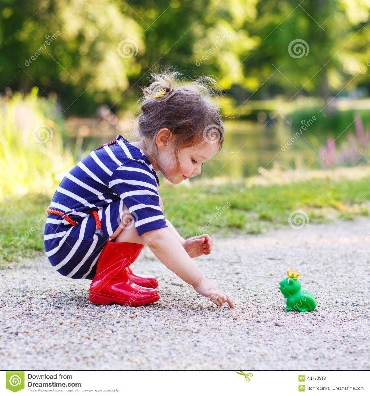 Beautiful Little Girl In Red Rain Boots Playing With Rubber Frog ...