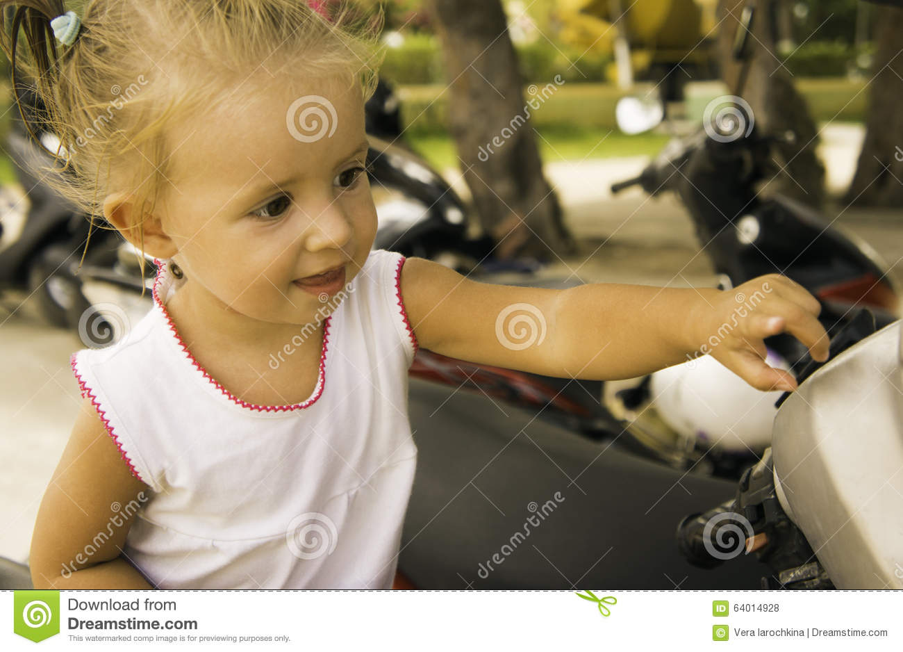 Beautiful little girl sitting on the bike in the park. she examines and studies it.