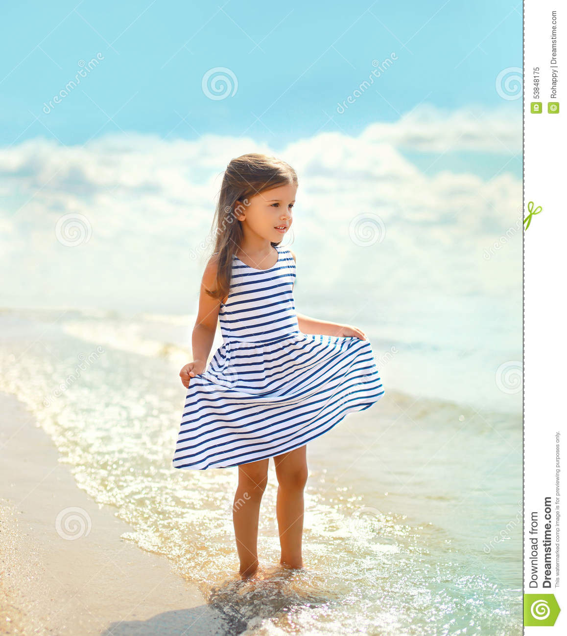 6a4872e57 Beautiful Little Girl In A Striped Dress Walking On The Beach Stock ...