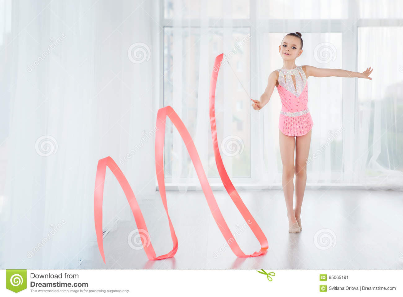 Beautiful little gymnast girl in pink sportswear dress, doing rhythmic gymnastics exercise Spirals with art ribbon