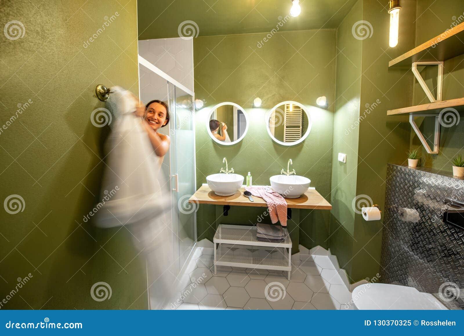 Green bathroom with woman in bathrobe
