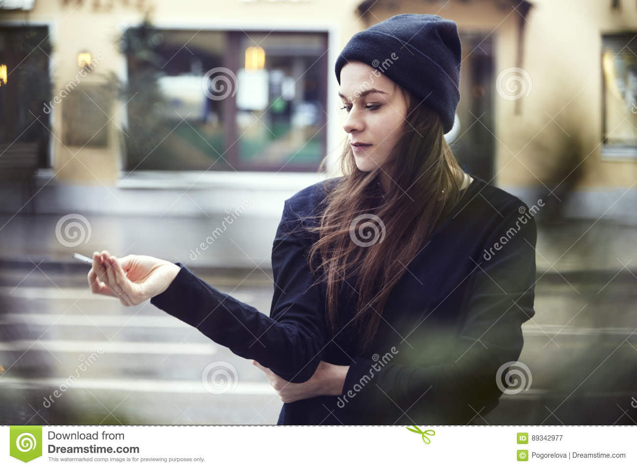 Beautiful lonely woman smoke outside at the street, cold weather in a city.