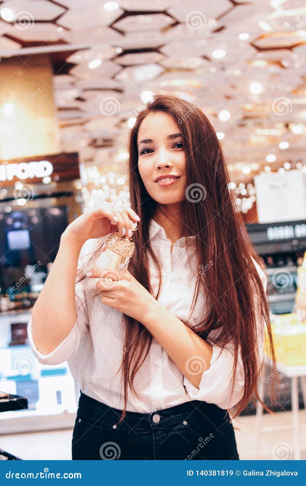 beautiful long hair asian smiling girl young woman in shop supermarket of cosmetics, perfumes, duty free