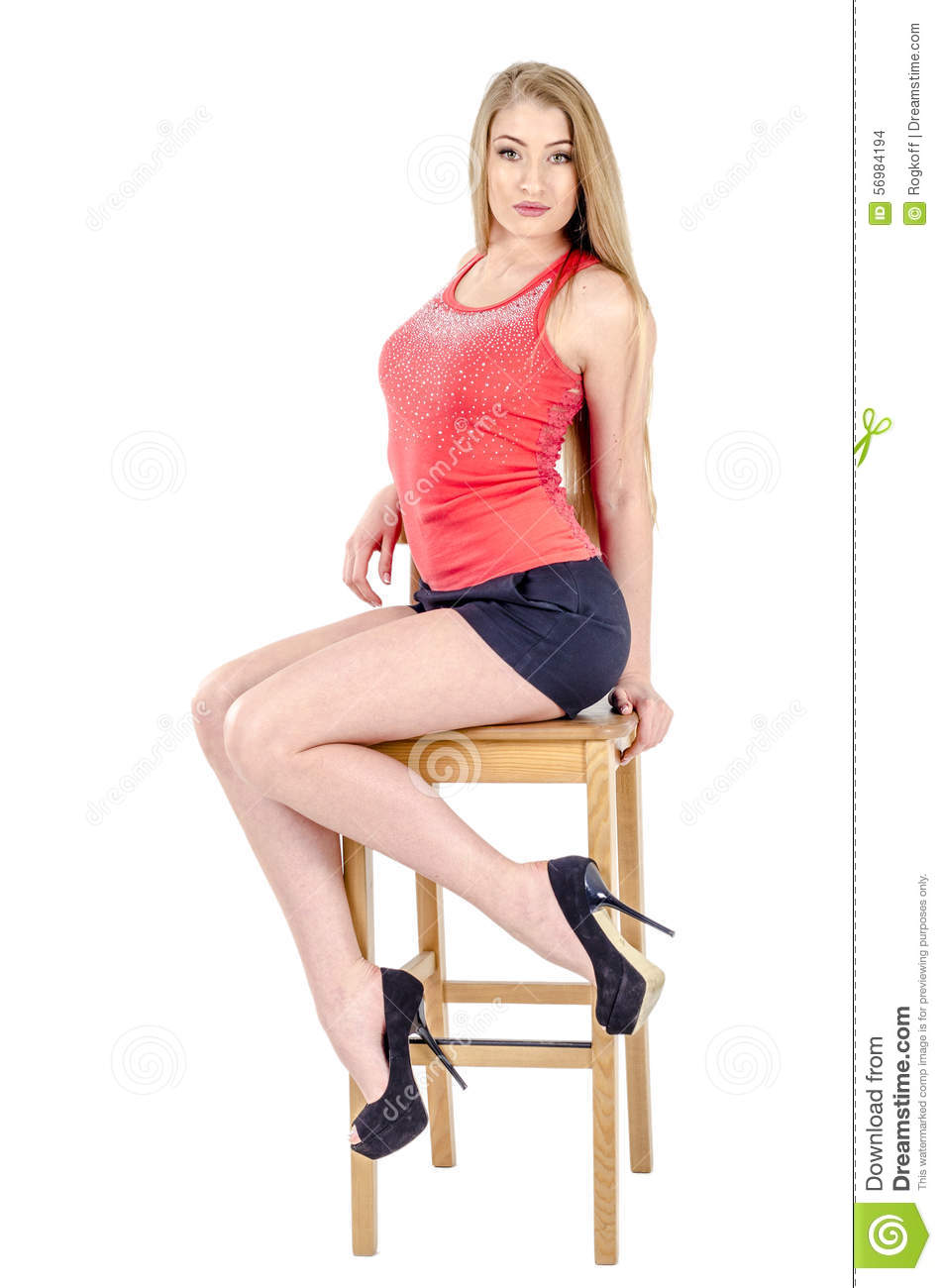 Original Blond Woman In Denim Miniskirt And Striped Shirt Sitting On A Banister