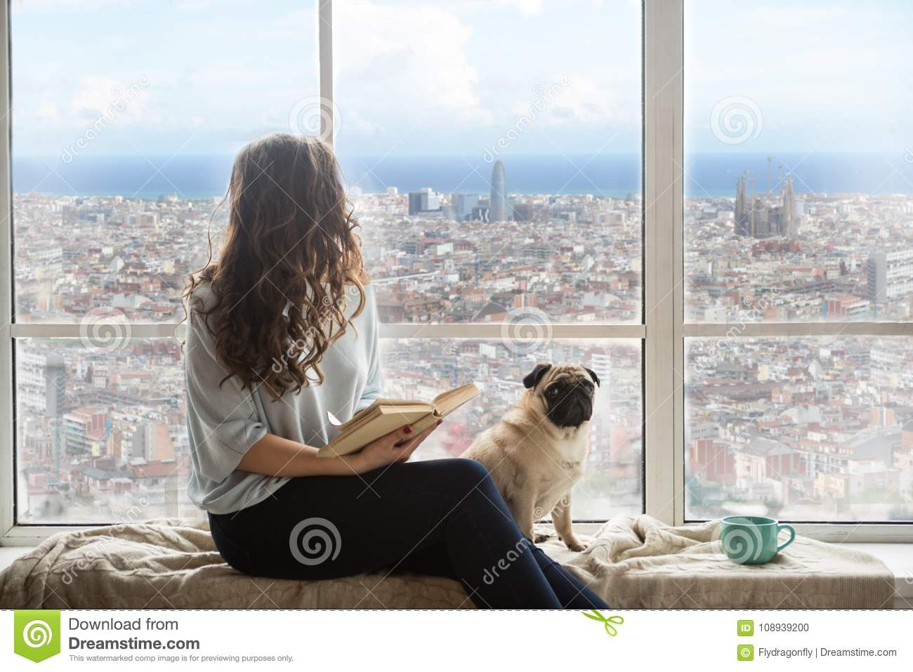 Beautiful long haired woman with her dog enjoying Barcelona Spain view outside the window
