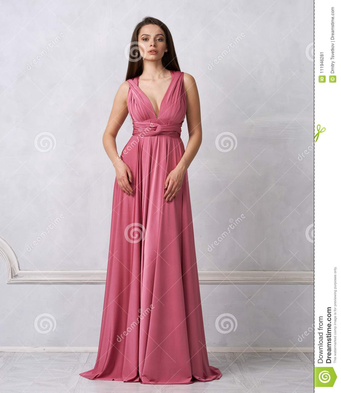 a7dddb2750 Beautiful long haired young woman dressed in stylish red bandeau maxi dress  posing against white wall on background. Elegant brunette female model ...
