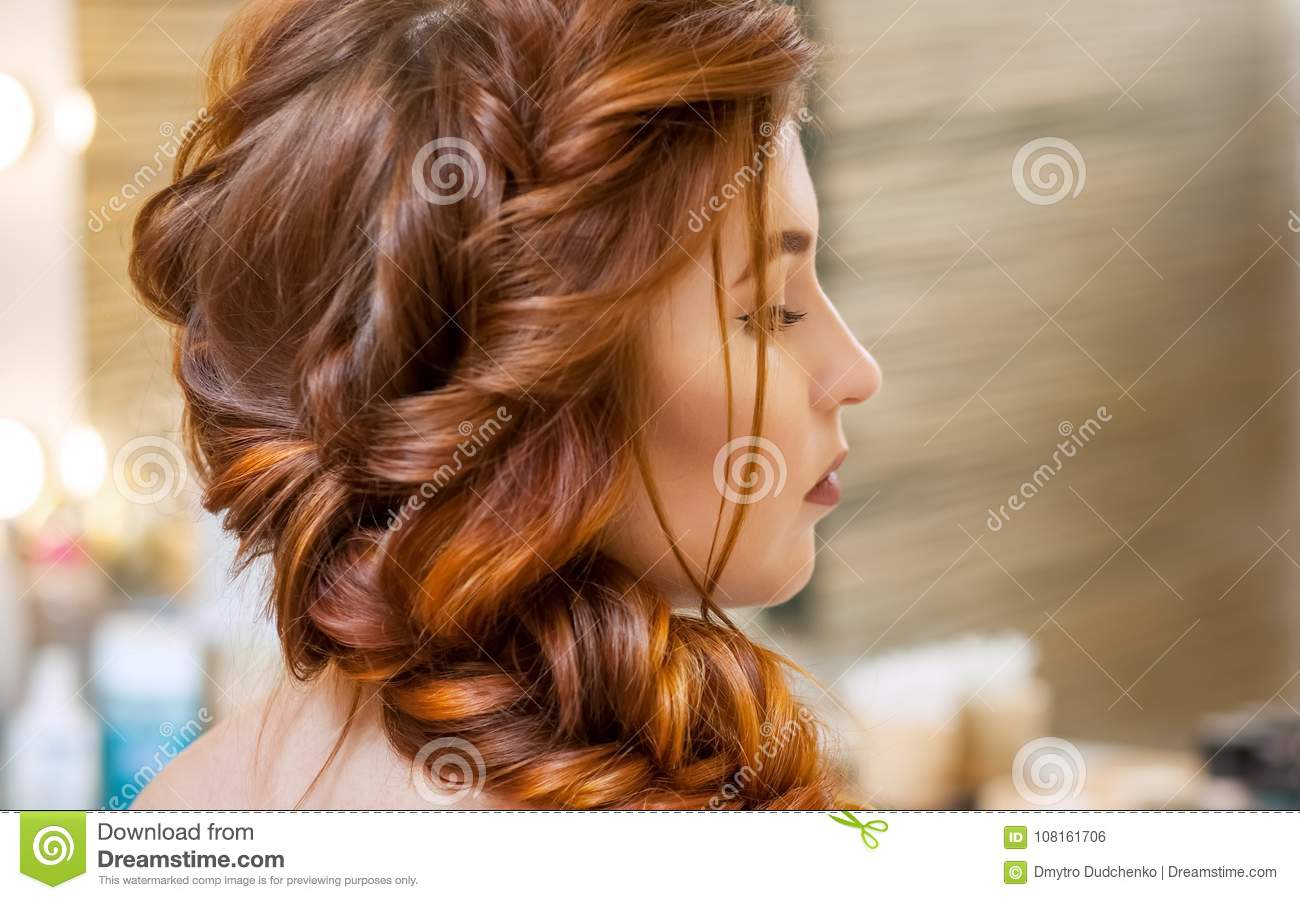 Beautiful, with long, red-haired hairy girl, hairdresser weaves a French braid, in a beauty salon.