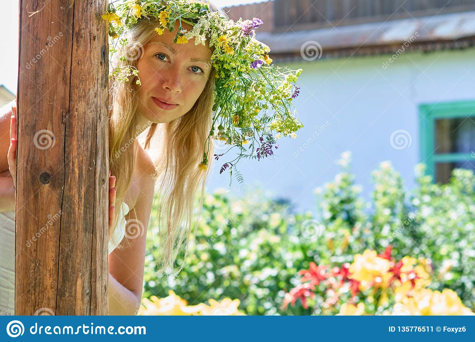 Beautiful long-white hair woman in white dress and flower wreath peeking playfully from behind a wooden pillar on yard of your