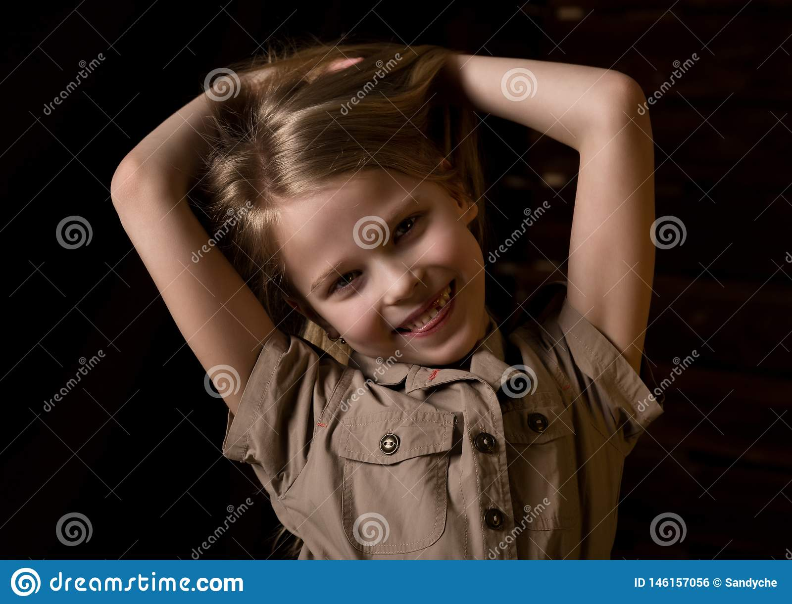 Beautiful lovely little blonde girl with different emotions on a dark background