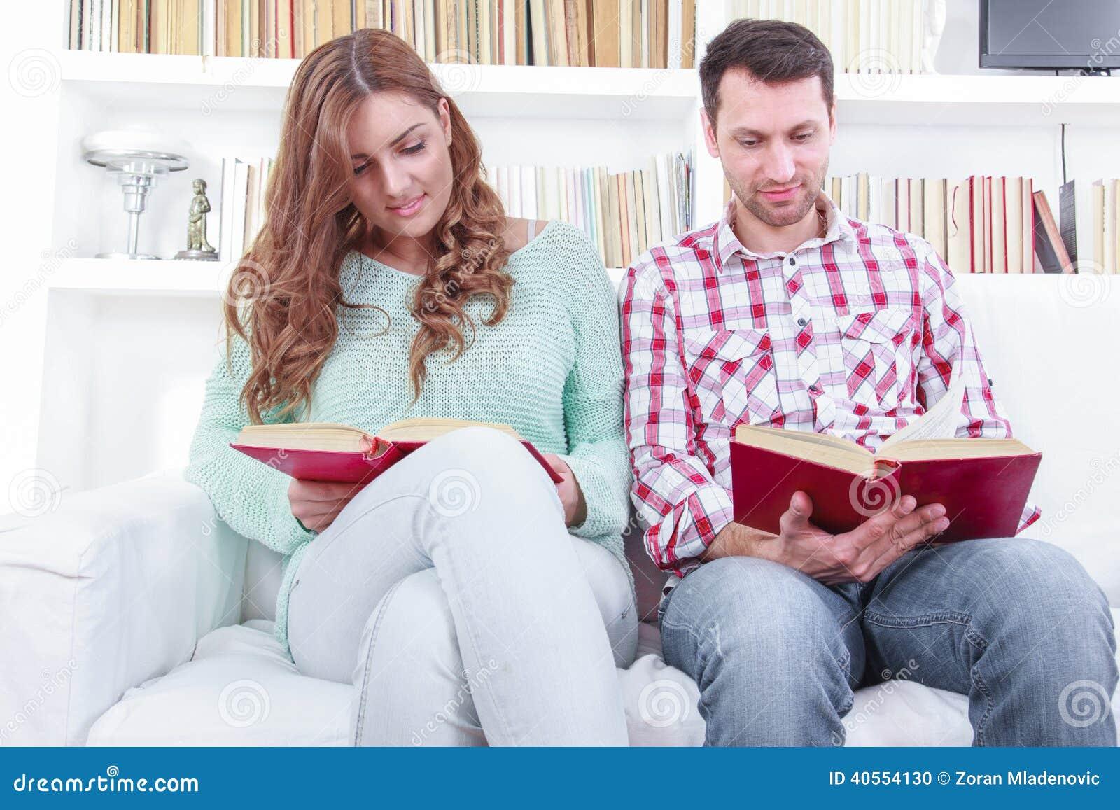 Beautiful loving casual couple reading a book on the sofa