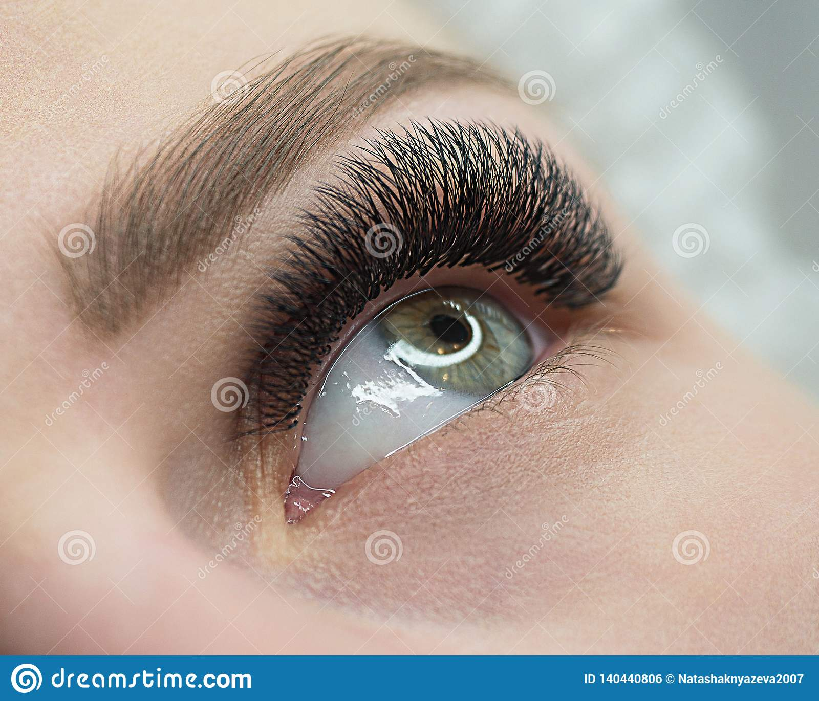 Beautiful macro shot of female open eye with eyelash extension. Natural look and bushy long lashes, close up, selective