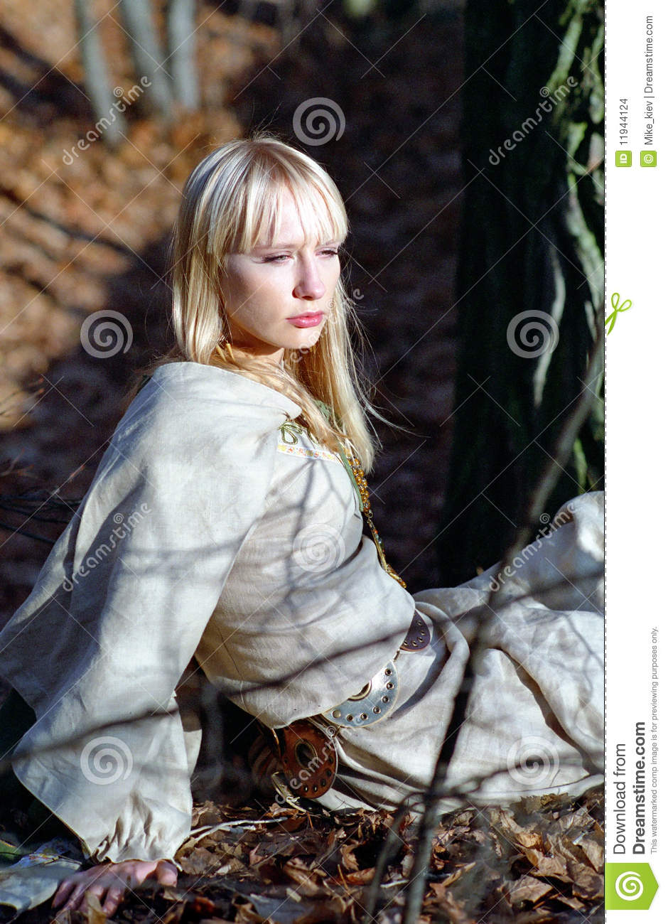 beautiful medieval woman sitting in forest stock images