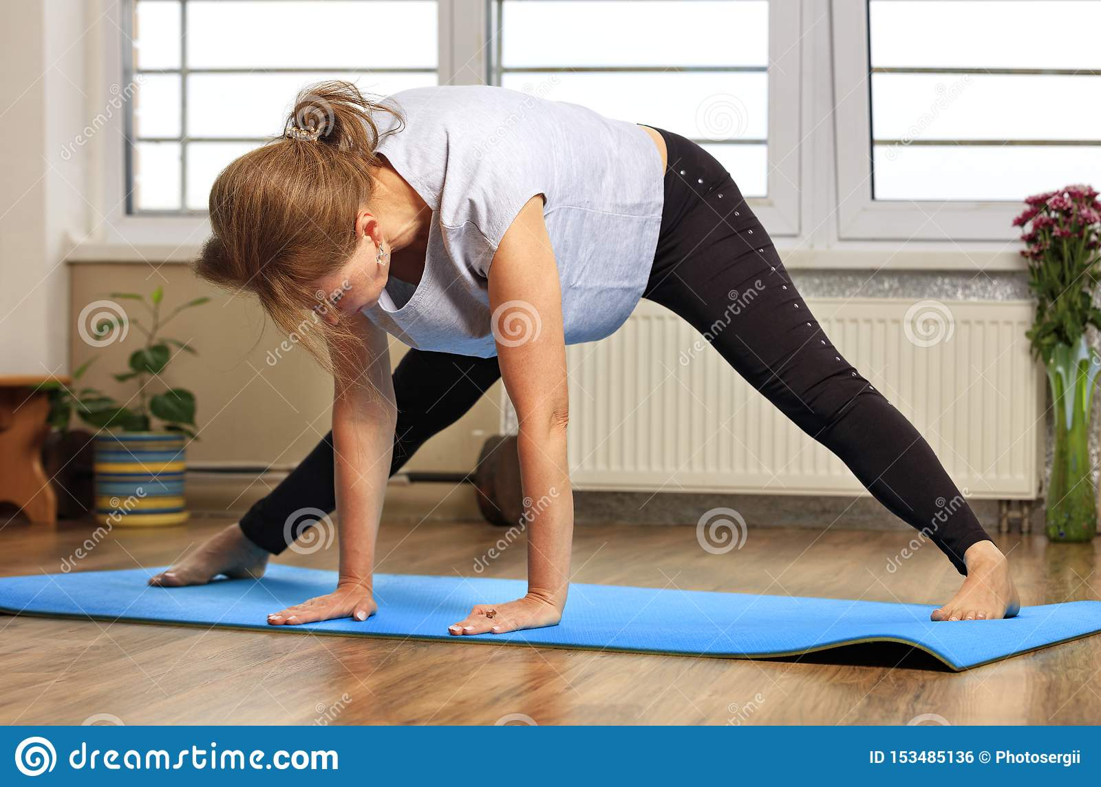 Middle aged or mature woman doing yoga indoors