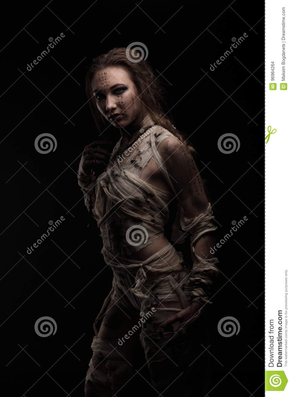 Beautiful model as egyptian mummy wrapped in bandages with hieroglyphics on skin.