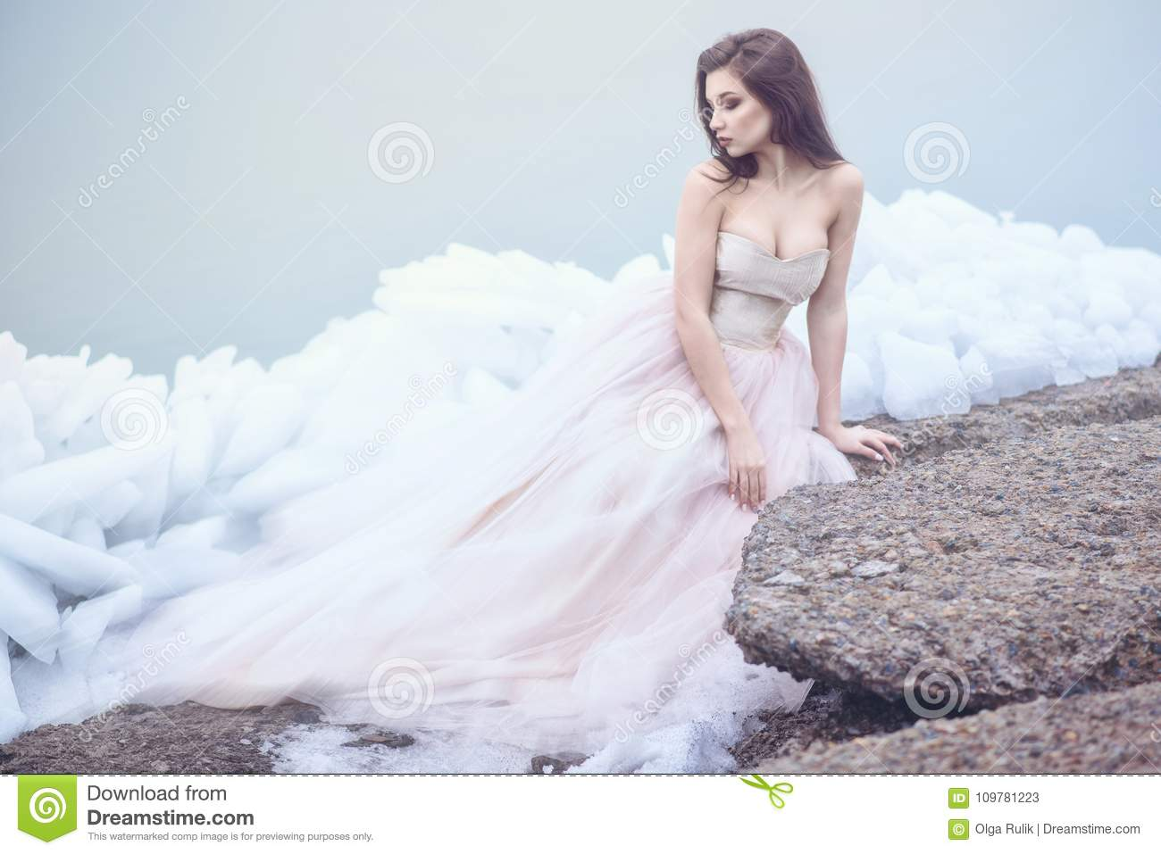 Beautiful model in luxurious strapless corset ball gown sitting on slabs of broken ice at the misty seaside