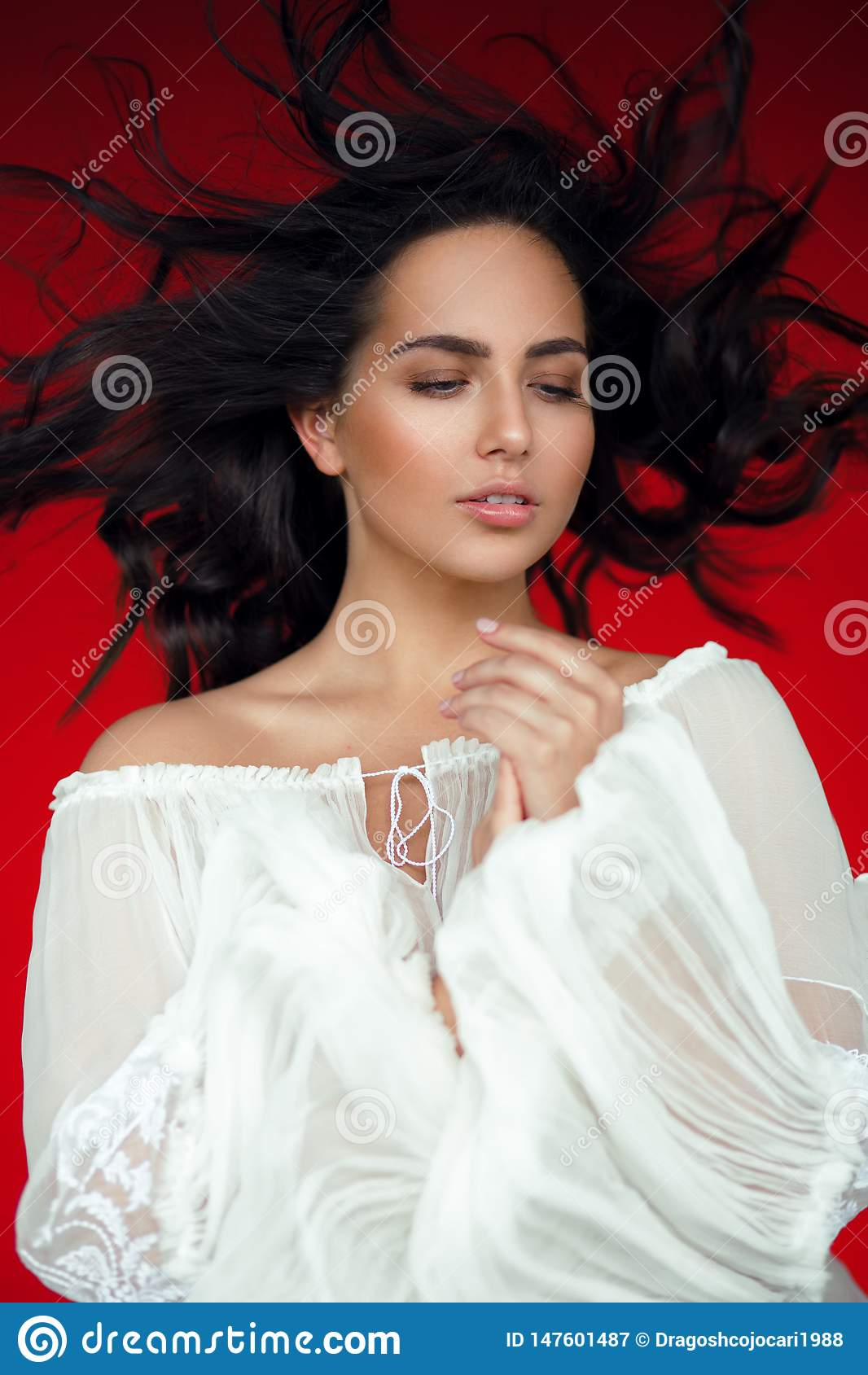 Graceful brunette woman,looking down, isoalted on a red background, straight flying his hair,