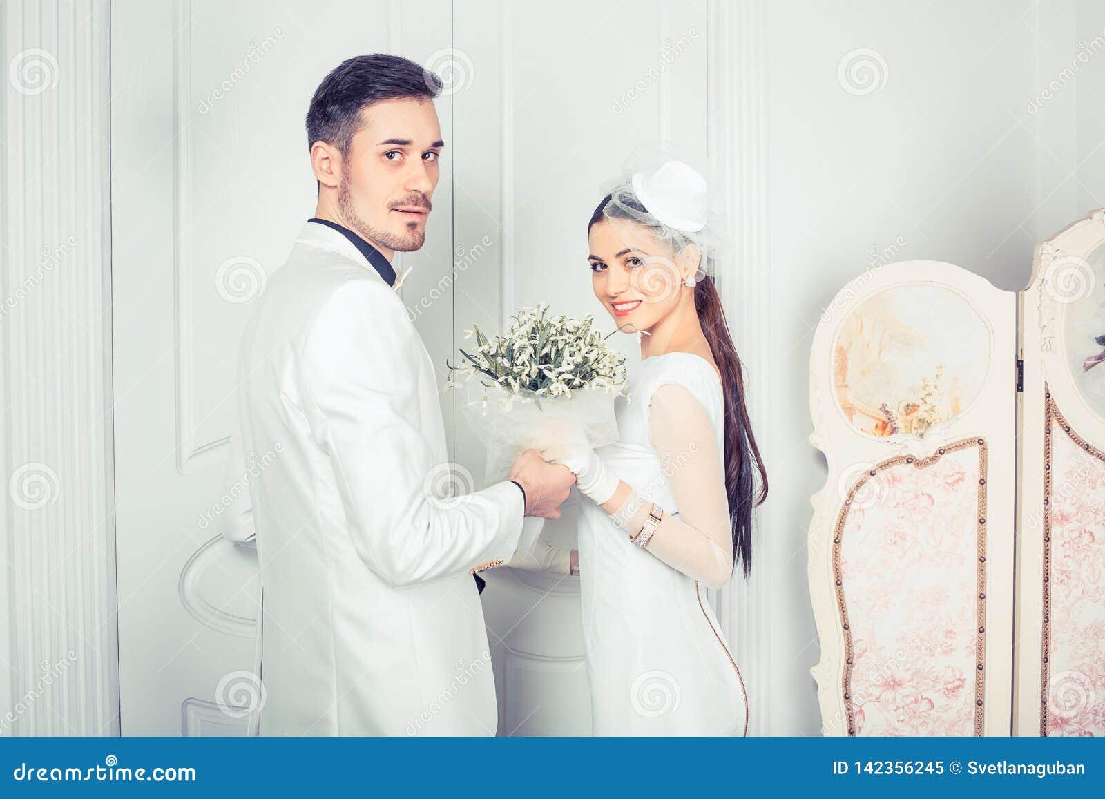 Beautiful modern newlyweds looking at camera