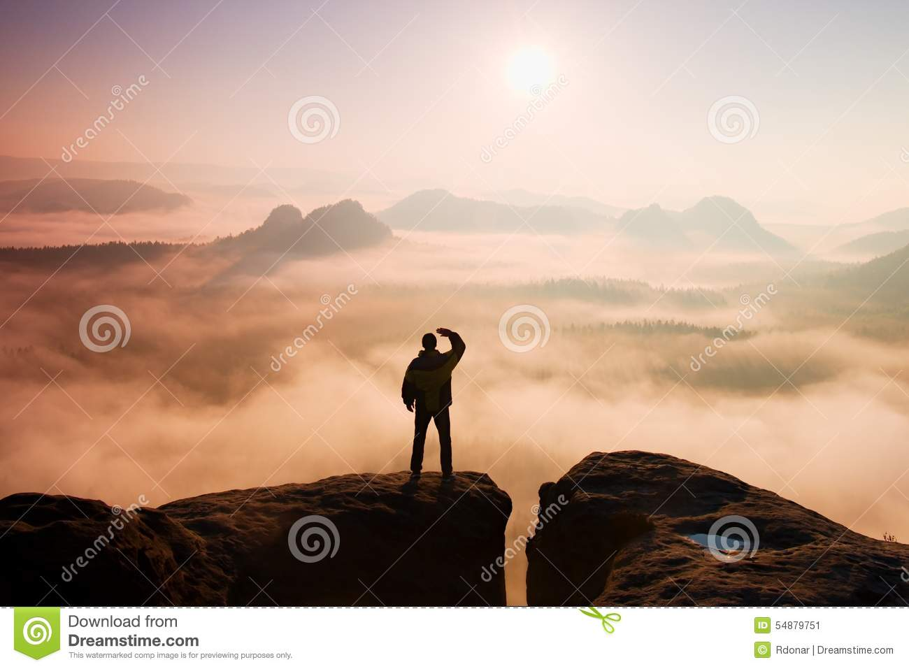 Beautiful moment the miracle of nature. Man stands on the peak of sandstone rock in national park Saxony Switzerland and watching