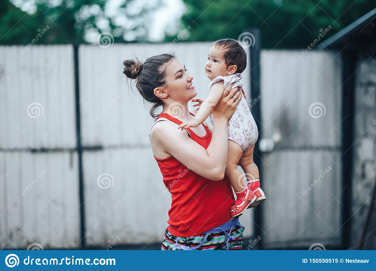 Beautiful Mother And Baby outdoors on the yard of house. Beauty Mum and her baby Child one year old playing in yard together. Mom
