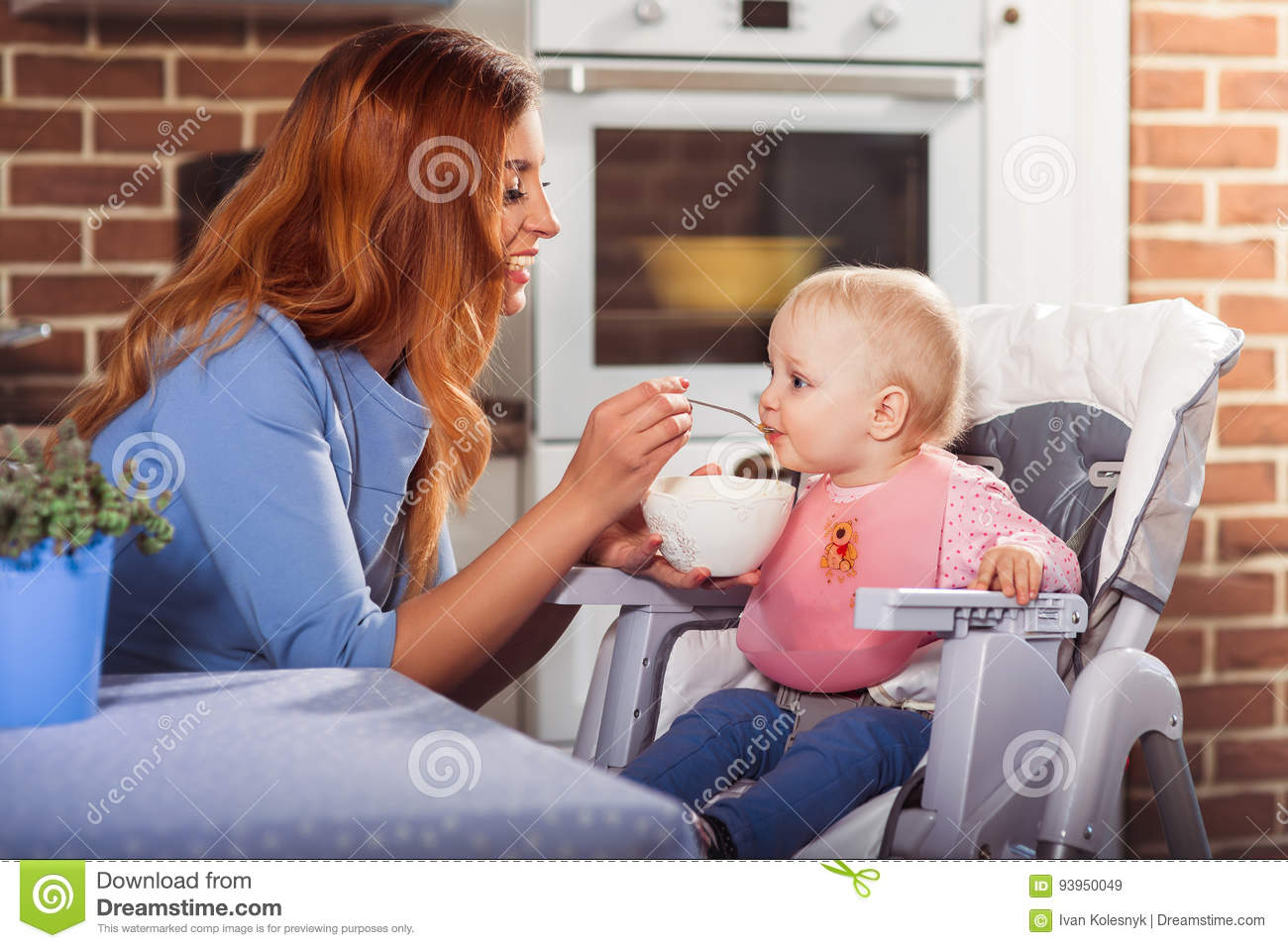 c1c07b66f Beautiful mother in blue dress feeding with spoon her cute baby girl witch  sits in high