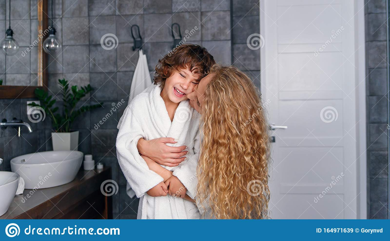 Beautiful Mother With Curly Hair In A White Bathrobe Hugs Her Little Smiling Son In The Bathroom Stock Image Image Of Cheerful Cozy 164971639