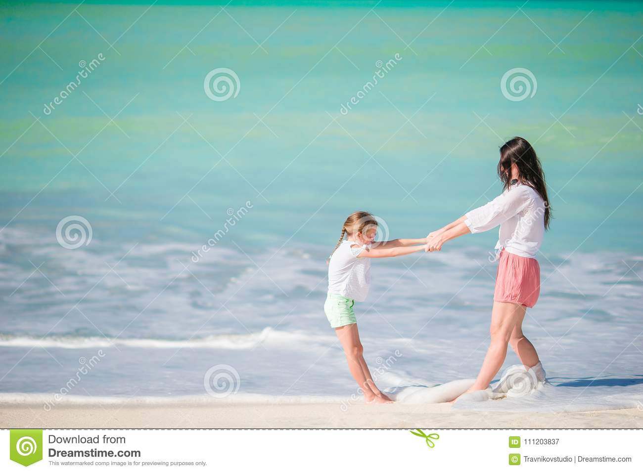 64f08a6f1549e Beautiful mother and daughter at Caribbean beach enjoying summer vacation.  Family walking on tropical famous