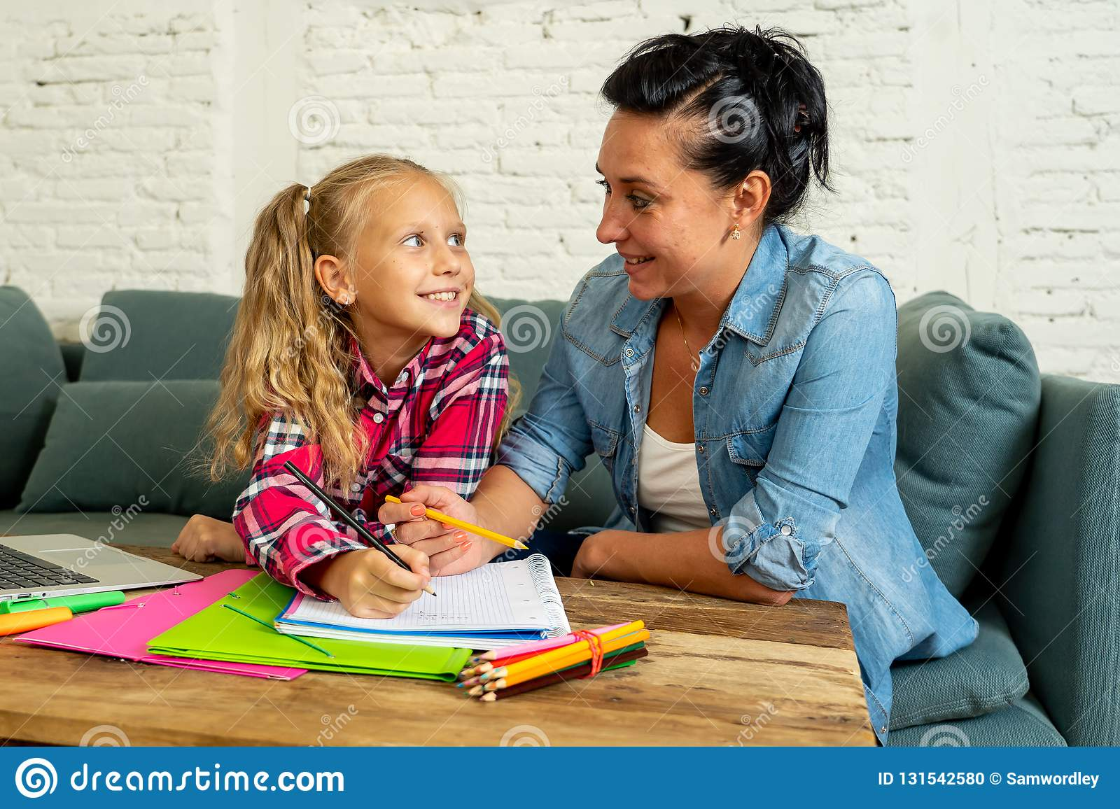 Beautiful mother helping her young blonde cute sweet girl to do homework at home in homework parenting and education concept