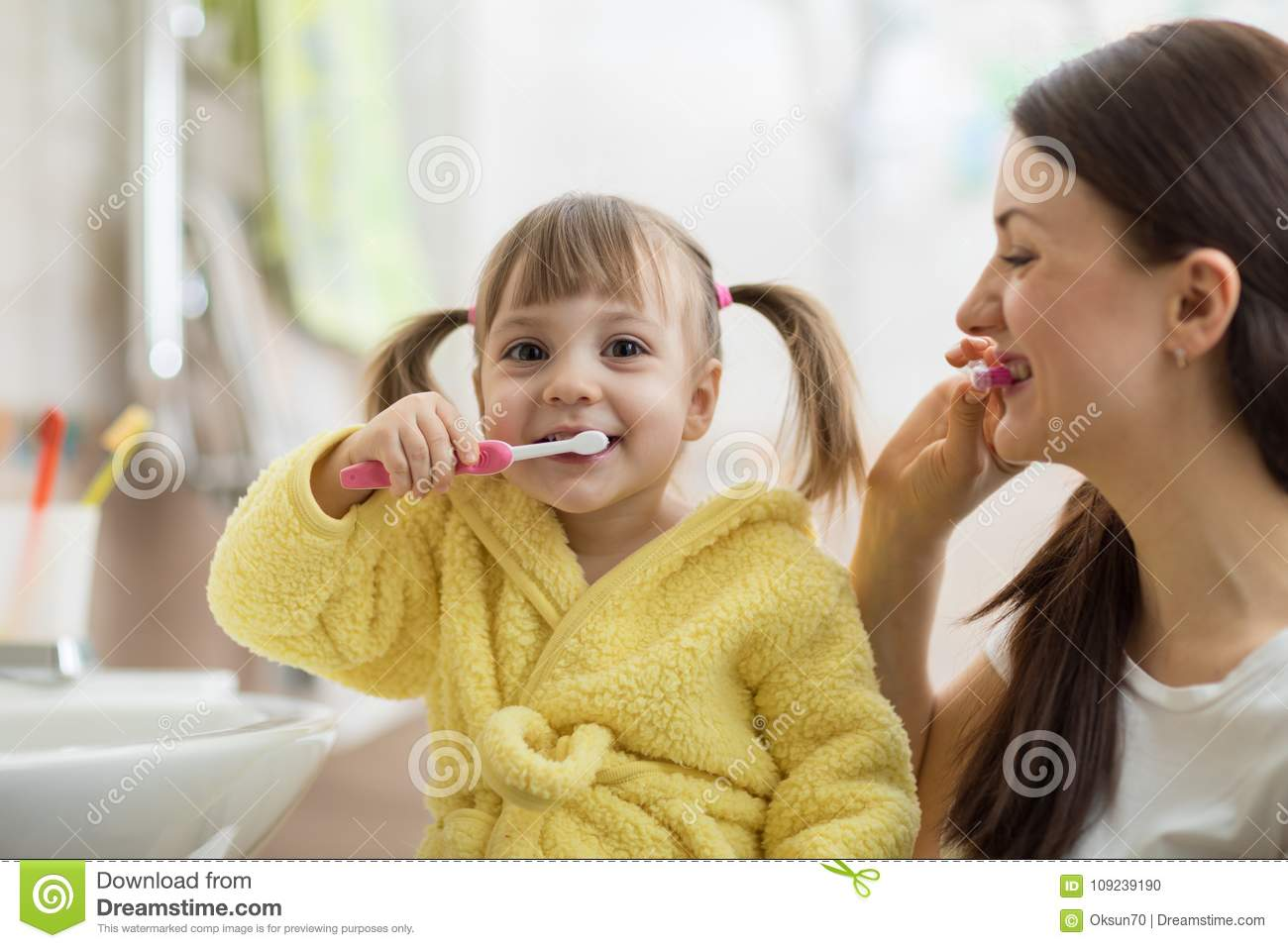 Smiling Child Kid With Her Mom Brushing And Clean Teeth In