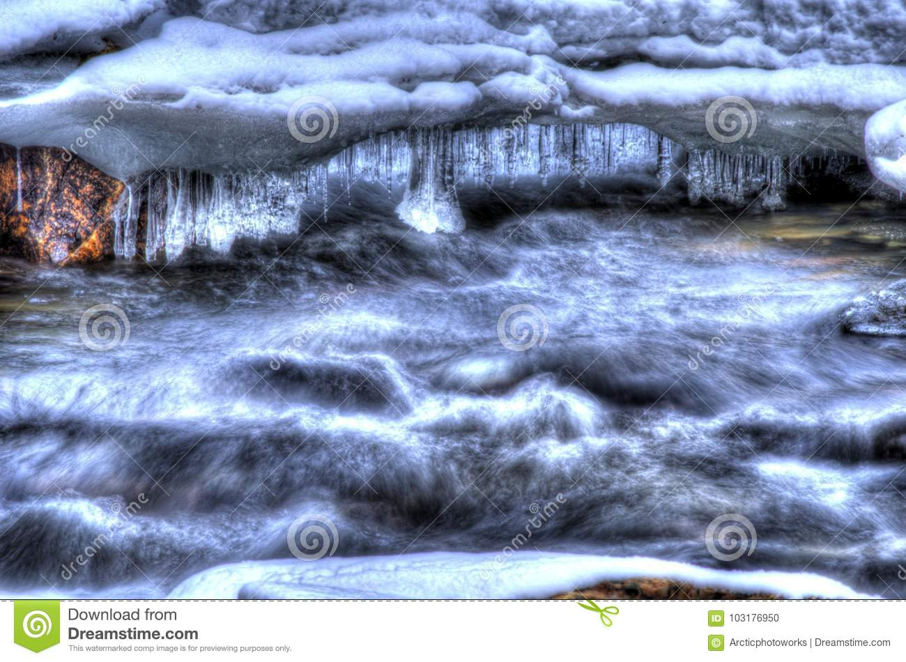 Beautiful mountain river stream in frozen winter landscape in the arctic circle with majestic long sparkling icicles