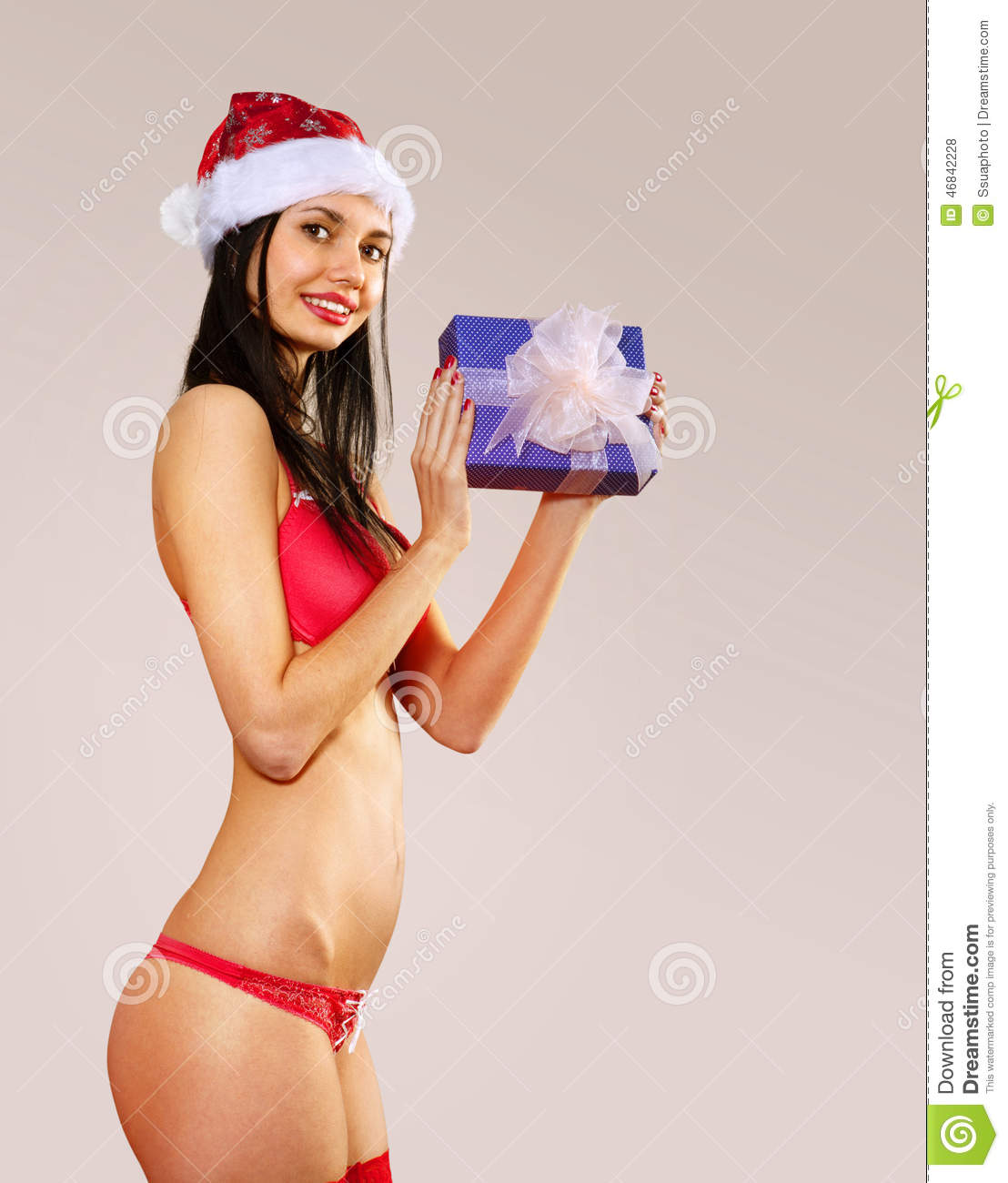 Beautiful mrs claus with gift wearing in red bikini costume isolated.