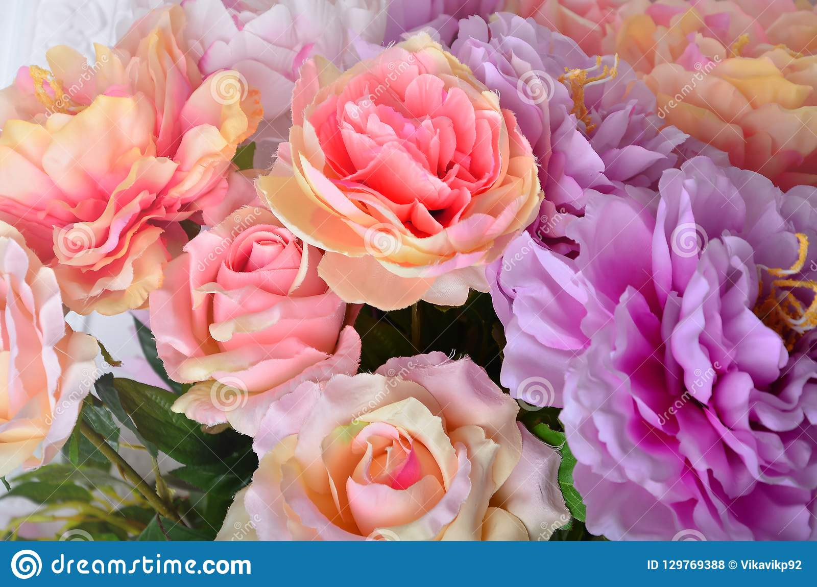 Beautiful multicolored artificial flowers background. flowers decor