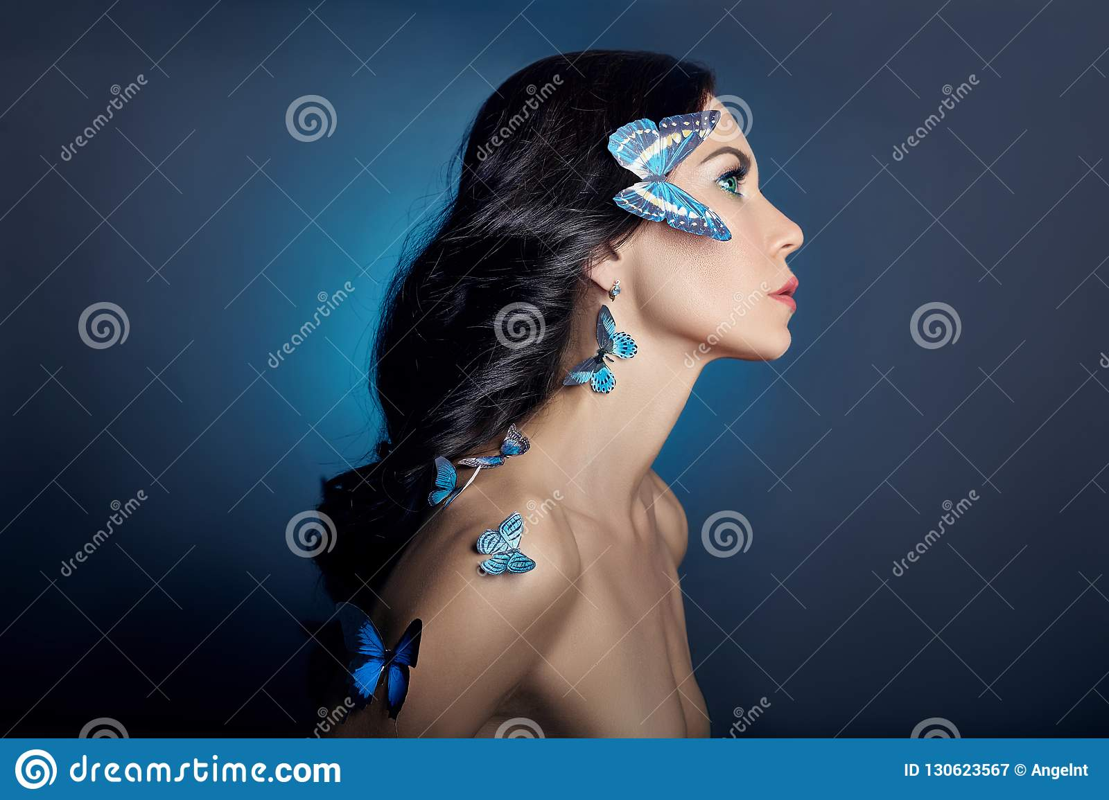 Beautiful mysterious woman with butterflies blue color on her face, brunette and paper artificial blue butterflies on the girls