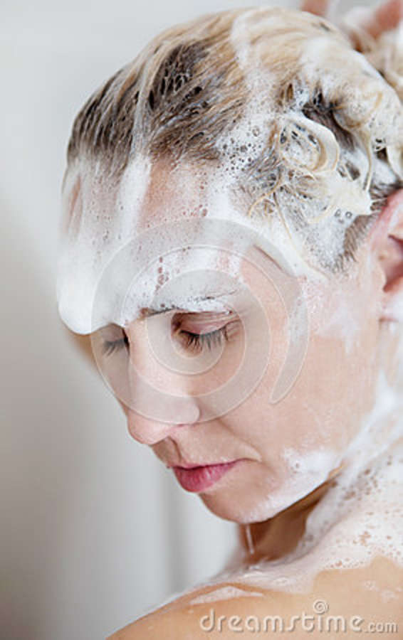 Naked woman showering in bathroom, rear view Stock Image