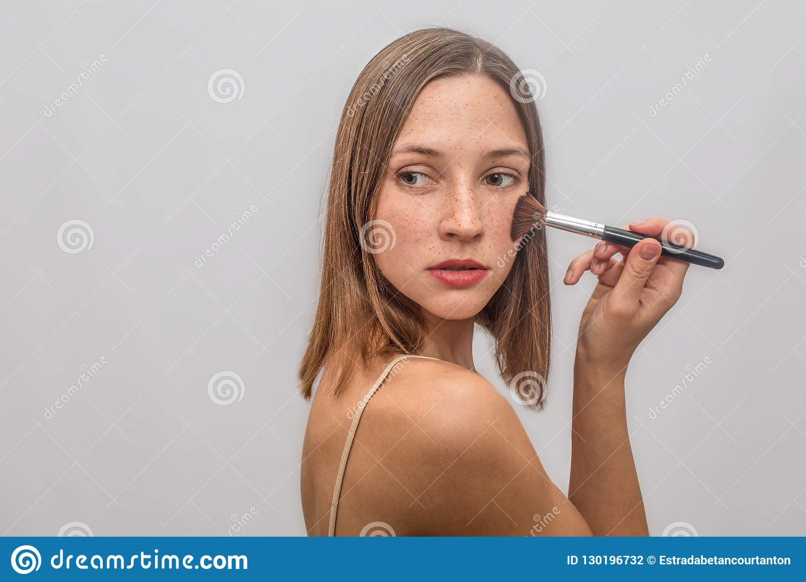 Beautiful and nice young woman stands and poses. She puts make up with brush on her chicks. She looks to left and turns