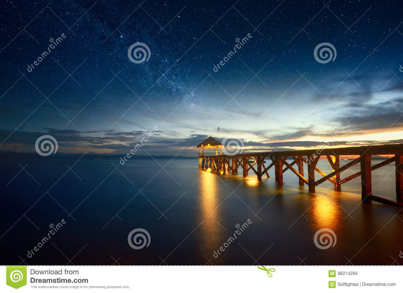 Beautiful night seascape with milky way in the sky and pier stretching into the ocean.