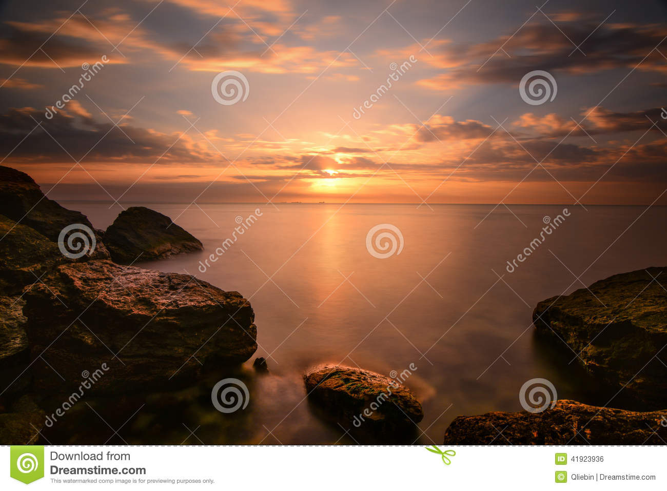 Beautiful ocean sunrise - calm sea and boulders stone coastline