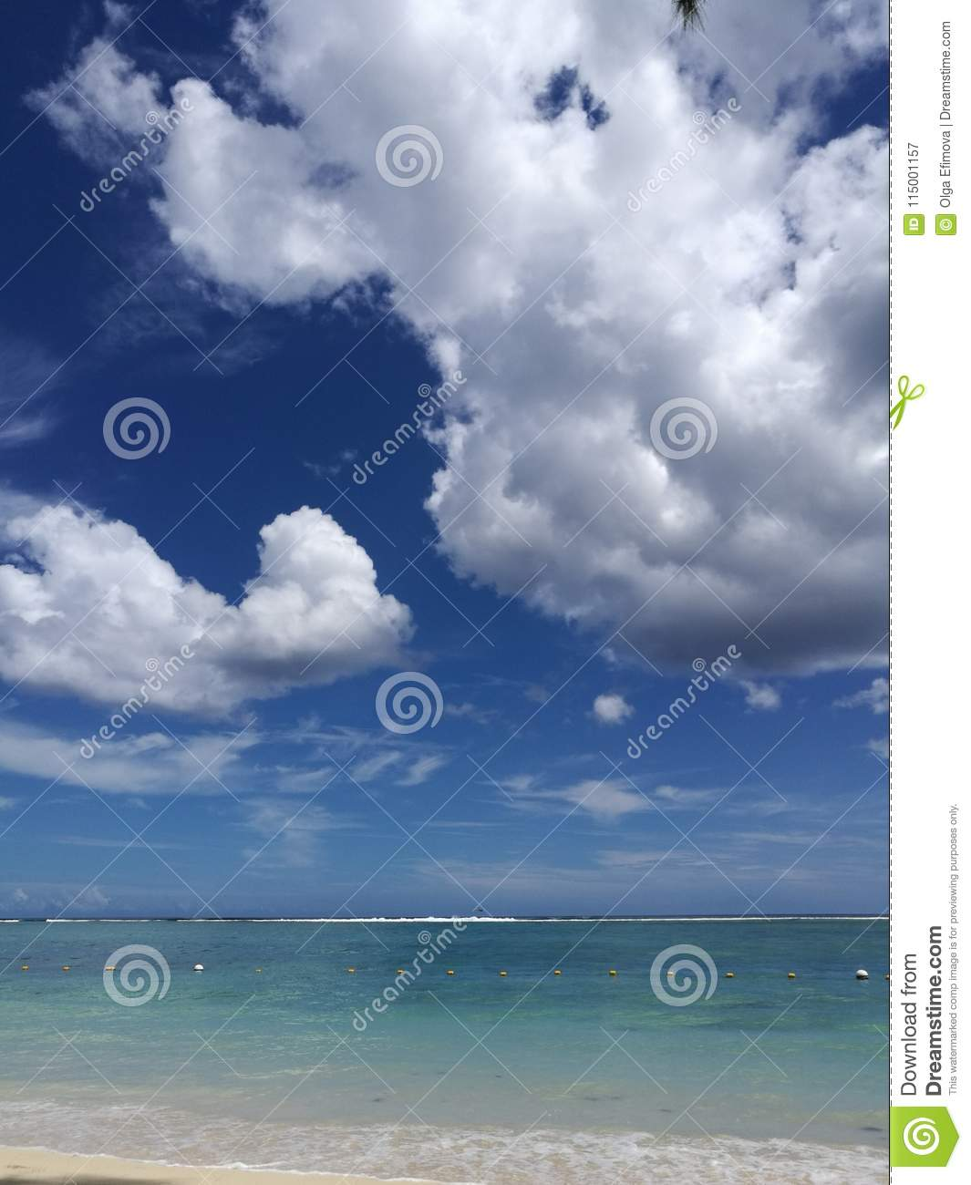 Beautiful ocean view with torquise water and dramatic clouds on sky