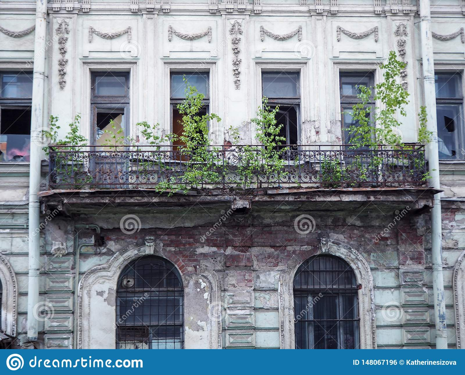 Beautiful old abandoned building with broken windows and a ruined balcony