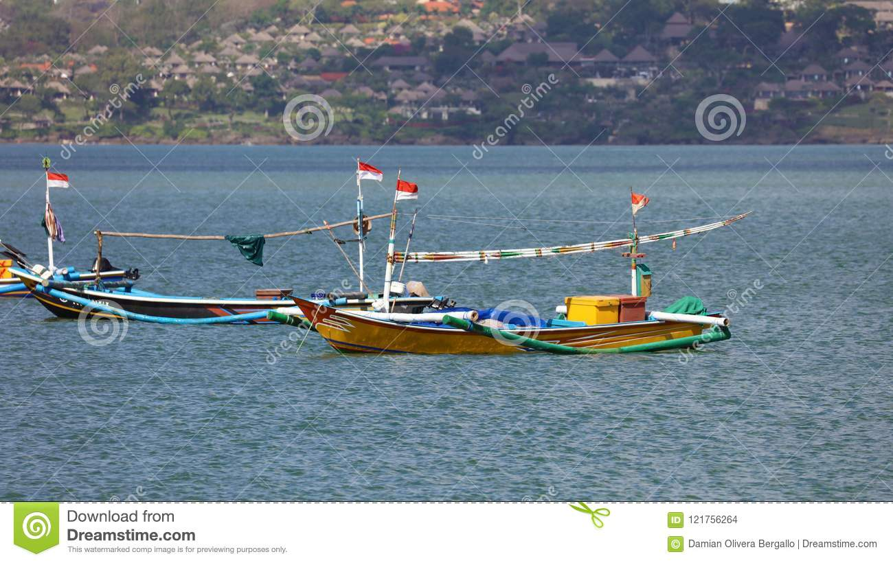 Beautiful picture of fishing boats at Jimbaran Bay at Bali Indonesia, beach, ocean, fishing boats and airport in photo.